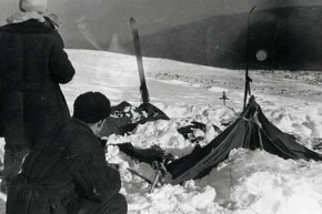Investigators at the site of the Dyatlov Pass incident examine the campers' tent, which had been cut open from the inside.