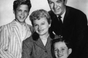 "Image Gallery: Parenting June Cleaver (played by Barbara Billingsley), surrounded by her adoring family, in this 1957 still from ""Leave it to Beaver."" With her always-clean house and her unflappable demeanor, she's one TV mom we'd like to be. See pictures of parenting."