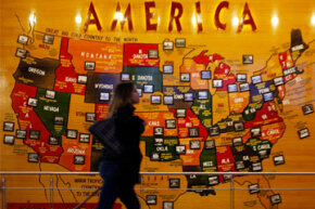 A passenger rolls past a map of the United States of America at Denver International Airport.