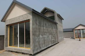 Two people visit a 3-D-printed house in Shanghai, China. The manufacturer says it can make 10 of these houses in a day.