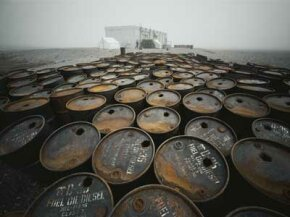 Discarded oil drums litter a desolate Alaskan coastline. See more oil field pictures.