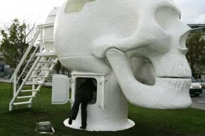 "A woman peeks inside Joep van Lieshout's ""Wellness Skull"" at the Karlsplatz in Vienna, during its 2008 exhibition there."