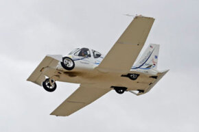 """The Terrafugia Transition """"roadable aircraft"""" flying high above the ground."""