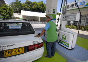 A gas station attendant fills up a taxi with liquefied petroleum gas. See pictures of alternative fuel vehicles.­