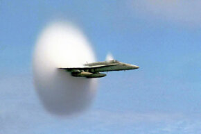An F/A-18 Hornet emerges from a cloud created when it broke the sound barrier.