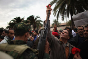 An image of peace from 2011's Arab spring. Here, a demonstrator places a flower in the barrel of a soldier's rifle after the ousting of Tunisia's then-president Zine al-Abidine Ben Ali. The Arab spring also created opportunities for groups like al-Qaida.