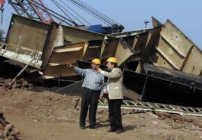 A Gujarat Maritime Board official and a shipbreaking captain discuss the details in front of a ship that will be scrapped, salvaged and recycled.