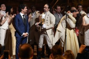 """Music director Alex Lacamoire and """"Hamilton"""" actor/composer Lin-Manuel Miranda celebrate onstage after winning a Grammy award in 2016."""