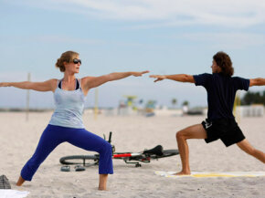 People in Miami Beach, Fl. take a yoga class on the beach to reduce stress.