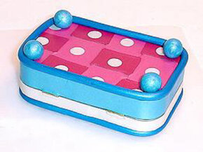 Desiree adds embellishments like feet made of clay balls to the bottom of her Altoids tin (shown upside down).