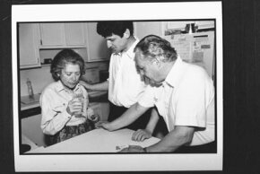 Shirley Gold, who has Alzheimer's, concentrates on taking a drink from a glass of water as her son and husband look on. See more brain pictures.