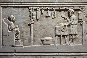 A butcher cuts up meat for a client in his shop in ancient Rome.