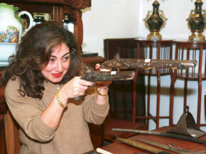 A Lebanese antique dealer examines a pair of 17th century gold and silver studded guns at a flea market that opened in the war-devastated city center of Beirut.