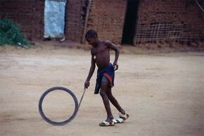 A young Cameroonian boy enjoys bowling a hoop -- just like children have for centuries.