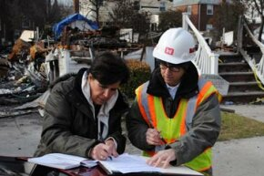 Martha Militano (left) signs a right-of-entry form authorizing the U.S. Army Corps of Engineers to remove the remains of her home after Hurricane Sandy.