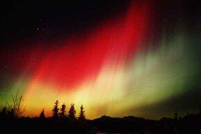 A glowing red aurora borealis appears in Denali, Alaska.