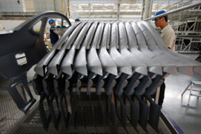 Workers at a Hyundai car factory line up pressed metal parts used in its car assembly line in Beijing, China.