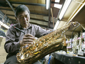 Third generation owner and head craftsman Zhang Zhong-Yao assembles a handmade saxophone at the Lien Chen Saxophone Company in Houli, Taiwan.