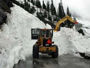 A bulldozer clears avalanche debris from a road in Glacier National Park.
