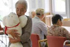 A retirement home resident cuddles a Paro. The FDA considers the faux harp seal a Class II medical device.