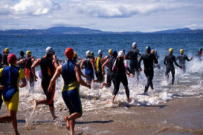 Triathletes in wetsuits head into the water, beginning the most dangerous leg of the race.