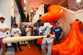 That's a big one! Yasiel Puig, No. 66 of the Los Angeles Dodgers, poses with an oversized bat during a visit to the MLB Fan Cave in New York City.