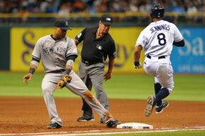 Infielder Robinson Cano, No. 24, of the New York Yankees covers first base as outfielder Desmond Jennings, No. 8, of the Tampa Bay Rays runs out a bunt. See more sports pictures.