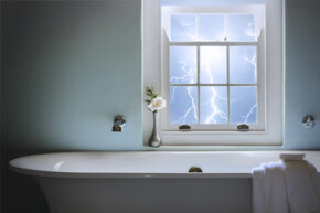 Bathtub with lightning in the background window