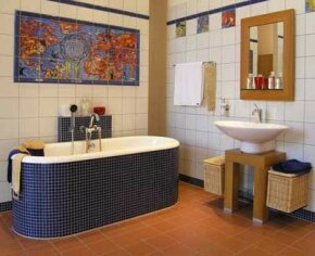 This easy-to-clean bathroom is tiled from floor to ceiling, including a unique tiled tub and decorative tile mural.See more pictures of bathroom decorating.