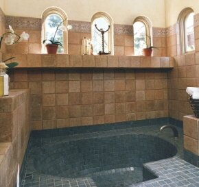 The mix of tiles in this bathroom gives the look of an ancient bathhouse.