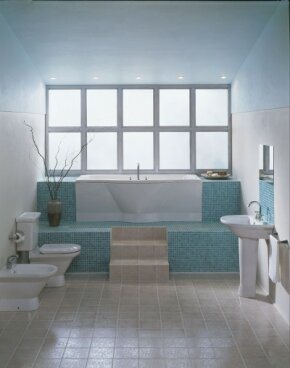 Tiles in warm and cool colors form an energetic back- ground for the all-white fixtures and walls in this bath.