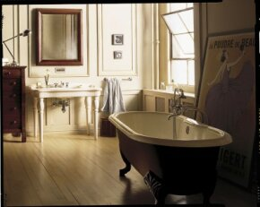 A traditional claw-foot tub and pedestal sink share space with a loft-type window and a modern lamp.