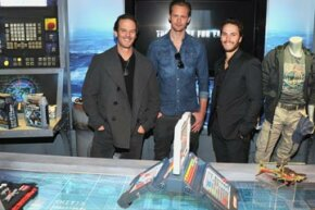 """Battleship"" director Peter Berg (left) with actors Taylor Kitsch (right) and Alexander Skarsgard (center) and the Deluxe Battleship Movie Edition game at Hasbro's American International Toy Fair showroom in New York, February 13, 2012."