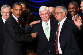 After signing the Wall Street reform bill they co-wrote into law on July 21, 2010, President Barack Obama congratulates Sens. Christopher Dodd and Barney Frank.