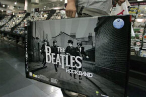 A man walks to a cash register to purchase The Beatles: Rock Band video game in a London store on Sept. 9, 2009.