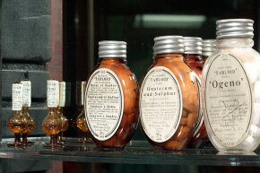 """The oval brown bottle in the center is labelled """"Tabloid guaiacum and sulphur"""" and dates back to the early 1900s. It was made by the pharmaceutical company Burroughs Wellcome & Co."""