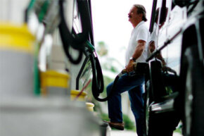 Charlie Sanchez fills his tank at a gas station in Miami, Fla.