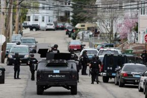 S.W.A.T. teams conduct a house-to-house search during the manhunt for a suspect in the terrorist bombing of the 117th Boston Marathon. See more police pictures.