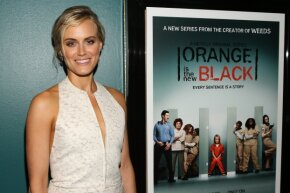 """Taylor Schilling, aka Piper Chapman on """"Orange Is the New Black,"""" poses next to a promotional poster."""