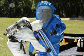 Firefighters help one another remove hazardous material protective suits to avoid self-contamination after responding to a simulated chemical attack during an anti-terrorism force protection exercise.