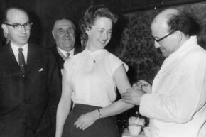 Dr Jonas Edward Salk (L), who developed the first vaccine against poliomyelitis, looks on as Dr J V Acius-Ferante vaccinates a woman.