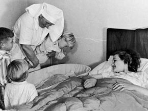 Three boys are introduced to their newborn baby sister by the midwife after a home delivery, August 1946.