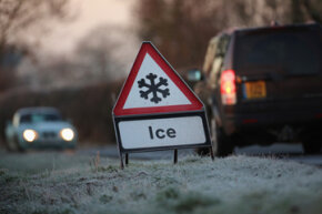 A warning triangle alerts drivers to an icy road in Knutsford, England.