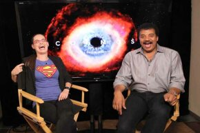 Astrophysicist/author Neil deGrasse Tyson (R) shares a laugh at Comic-Con in San Diego, California in 2013.