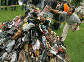 "Edgar Moreno, victim of a landmine blast, places a flag bearing the words ""No more anti-personnel mines"" on a heap of shoes in Bogota, Colombia."