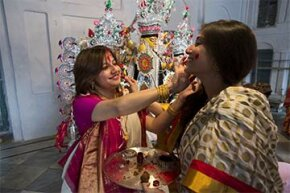 Married women smear vermilion on each other's faces as a part of farewell rituals on the last day of the Hindu Durga puja festival in India.