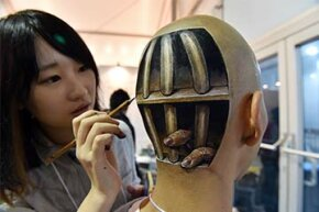 Japanese body-painting artist Hikaru Cho adds the finishing touches to a painting on the head of Ryonosuke Tanaka during Tokyo Designers Week in Tokyo, 2014.