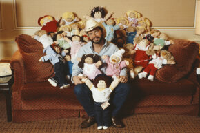 Cabbage Patch Doll creator Xavier Roberts sits amongst a group of Cabbage Patch Kids in 1983.
