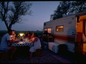 A family enjoys dinner outside their camper at the Antelope Valley RV Park.