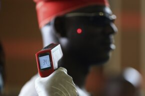 A man has his temperature taken using an infrared digital laser thermometer at the Nnamdi Azikiwe International Airport in Abuja, Nigeria, on Aug. 11, 2014. Fever is one of the early symptoms of Ebola.